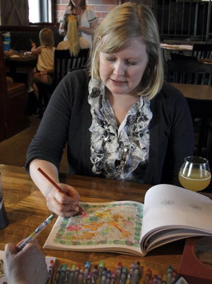Sarah Becker colors at Reclaimed Rails during the adult coloring event on Wednesday, June 21.