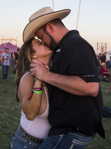 Kelsy Stephens and Max Baumann kiss during Cody Johnson's performance during Country Thunder Arizona on Saturday, April 7, 2018, in Florence, Arizona.