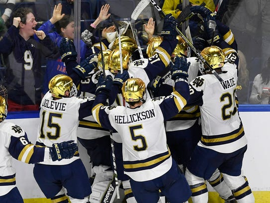 Notre Dame players celebrate their win in overtime of an NCAA college hockey regional tournament game against Michigan Tech.