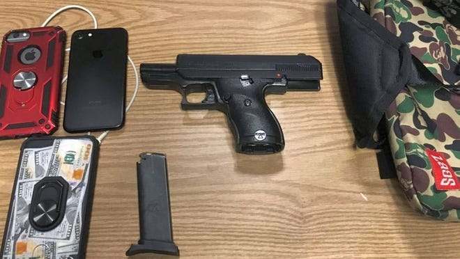 Massachusetts State Police issued this photo of a gun and cellphones seized in a traffic stop Wednesday in Fitchburg.
