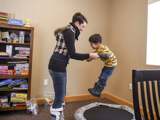 Cari Brown helps her son Craig Brown, 4, jump on the