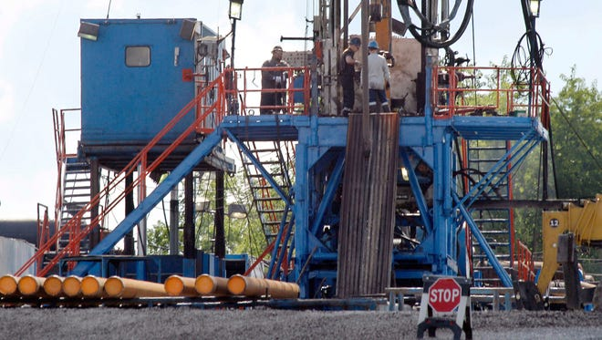 A crew works on a gas drilling rig at a well site for shale based natural gas in Zelienople, Pa. in this June 2012 file photo. Increased U.S. oil and gas production is contributing to a decline in world oil prices.