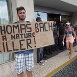 "A protester holds a banner that reads: ""Thomas Bach is a Nature Killer"" as police guard the entrance of the hotel where International Olympic Committee meeting in Rio de Janeiro, Brazil, Saturday, Feb. 28, 2015."