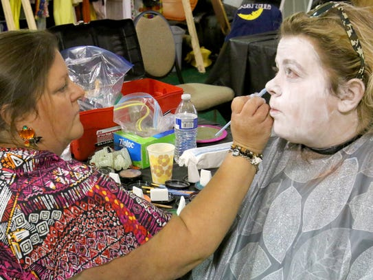 Michelle Kringel of West Bend applies a base of cake makeup to daughter Alycia Kringel as one of the characters at The Haunt.