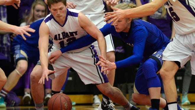 Albany's Kyle Birr (12) battles Braham's Connor Tschumper (0) for a loose ball in the first half of their Sect. 6-2A championship game March 4 at Halenbeck Hall.