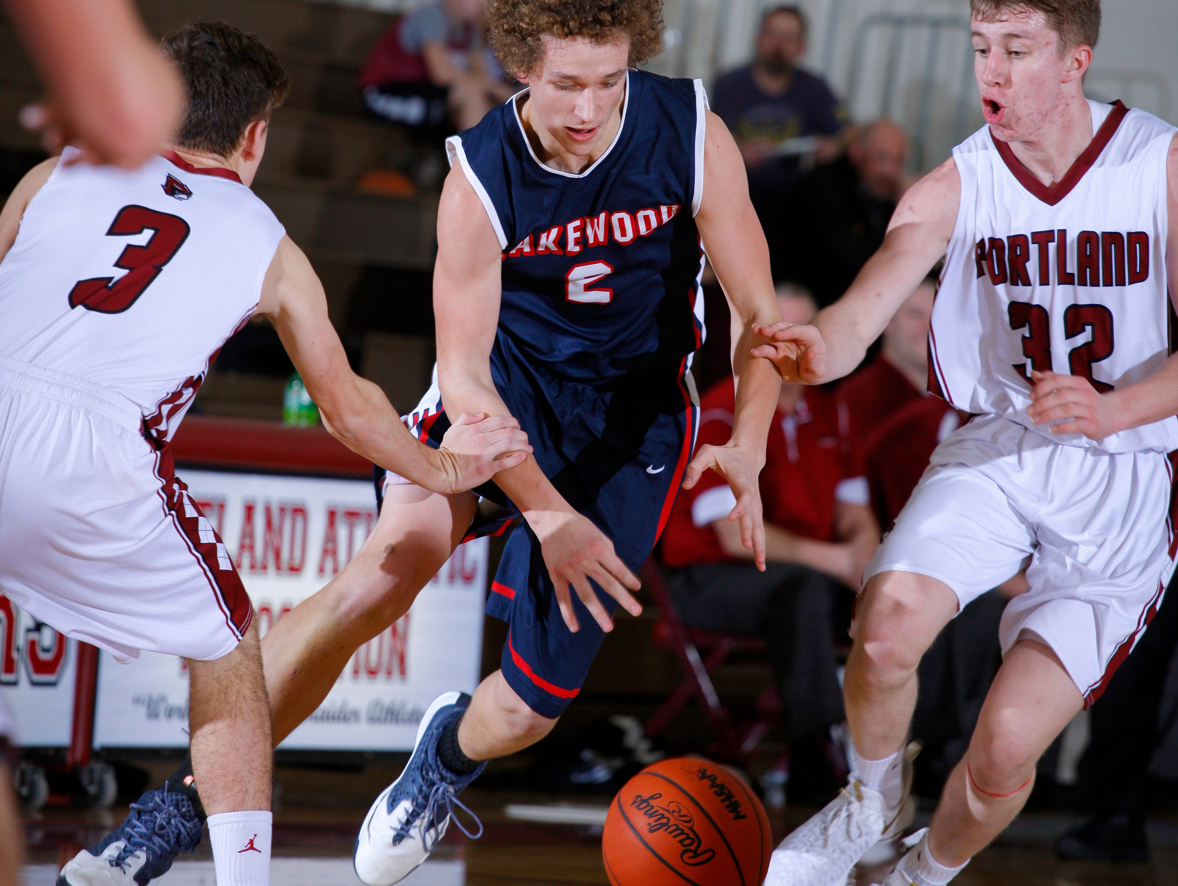 Lakewood's Josh Campeau, center, and Portland's Brett Pung, left, and Bobby Brandsen, right, chase the ball Tuesday, Jan. 31, 2017, at Portland High School. Portland won 53-44.