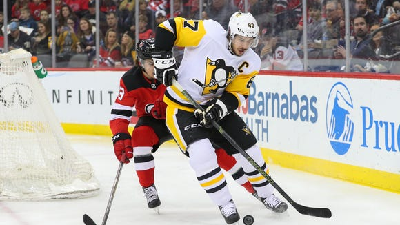 Pittsburgh Penguins center Sidney Crosby (87) skates with the puck defended by New Jersey Devils center Nico Hischier (13) during the first period at Prudential Center.