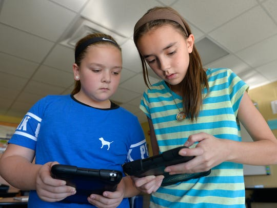 South Junior High School sixth-graders Mykenna Watkins, left, 11, and Jaelyn Plantenberg, also 11, compare notes on using their Apple iPad Minis for assignments Tuesday, Oct. 13 in Garrick Grace's C4 (Community, College, Career, Citizenship) class. If the referendum passes, all middle school students may get full-sized iPads. Currently all ninth-graders get MacBook Air laptops. Under the referendum, that would expand to other grades and other technology may be updated.