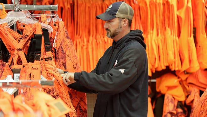 Jeremy Jelinek from Menasha shops for blaze orange in preparation for the upcoming deer gun season at Fleet Farm in Grand Chute.