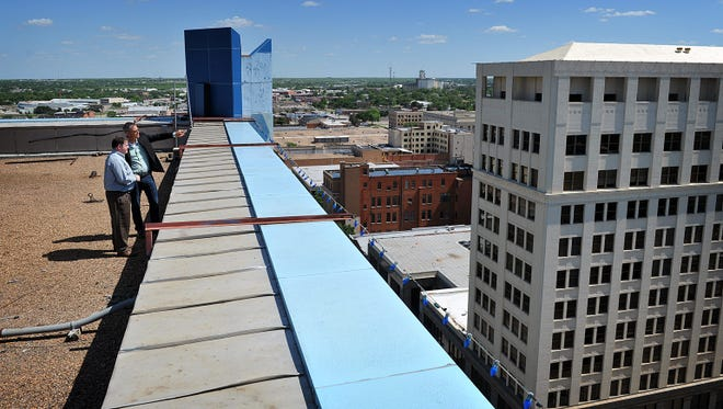 Wichita Falls Chamber of Commerce and Industry President Henry Florsheim, left, and Will Kelty, owner of the First Wichita Building, enjoy the view from the building's roof. In recent years Kelty's company has purchased several buildings near by, including the 10-story former hotel across the street. Kelty hopes to add residential complexes along with the office and retail spaces under construction.