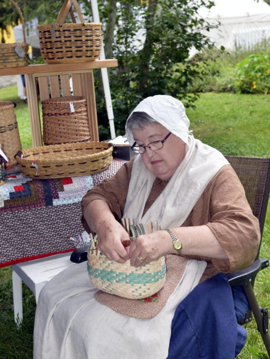 Abby Eberly of East Earl weaves a basket during the 47th Annual Harvest Fair held at the Historic Alexander Schaeffer Farm on Saturday.