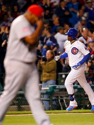 Chicago Cubs right fielder Jorge Soler, right, runs the base path after a home run given up by Cincinnati Reds relief pitcher Jumbo Diaz, left, during the eighth inning of a baseball game in Chicago, on Monday, April 13, 2015.