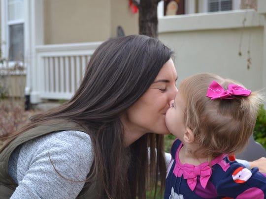 Alisa Hardy Orton kisses her daughter Emmeline.