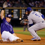 Colorado Rockies' DJ LeMahieu slides safe into third for a triple as Los Angeles Dodgers third baseman Juan Uribe (5) fields the late throw during the second inning of the game Monday, Sept. 15, 2014, in Denver.