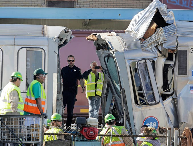 Workers inspect the wreckage of two Chicago Transit Authority trains after a collision Sept. 30 in Forest Park, Ill. Thirty-three people were injured when a westbound train stopped at the CTA Blue Line Harlem station was struck by an eastbound train on the same track.