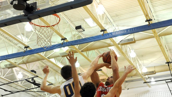 West Muskingum's Drew McKenzie contests a shot by Coshocton's Dallas Griffiths in Tuesday's game.
