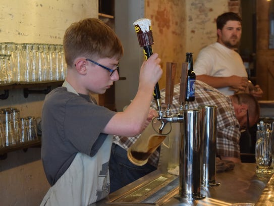 Parker Argyle pours a draft root beer during the grand