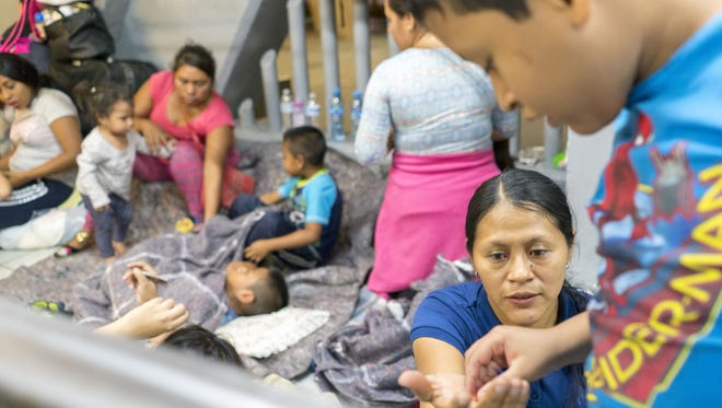 El Salvadorian Teresa Hernandez Reyes and her son Fernando Zepeda Hernandez, 8, get help from a Christian humanitarian group while they and other migrants from Central America wait in line to ask for asylum outside U.S. Port of Entry in Nogales.