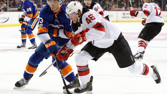 New York Islanders center Mathew Barzal (13) defends New Jersey Devils center Blake Speers (46), impeding Speers's progress to the puck with his stick during the third period of a preseason NHL hockey game in New York, NY, Monday, Sept. 25, 2017. The Islanders shut out the Devils 3-0. (AP Photo/Kathy Willens)