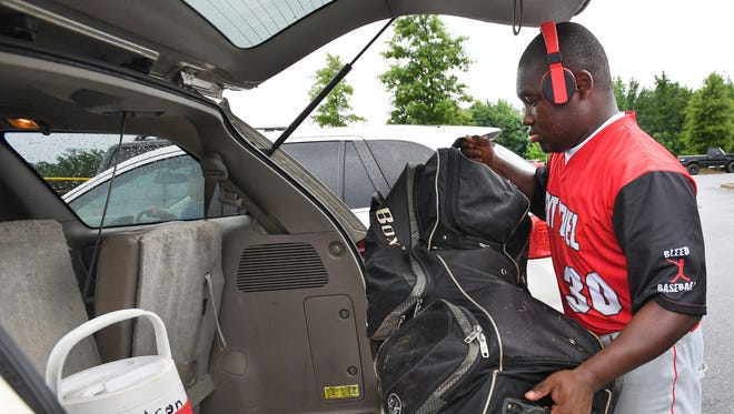 Eric Hudson, Jr., who plays for the Next Level Fire baseball team from Charlotte, loads his equipment into his father's van after the team's game at Conestee Park in Greenville was canceled due to rain on Thursday, June 22, 2017.