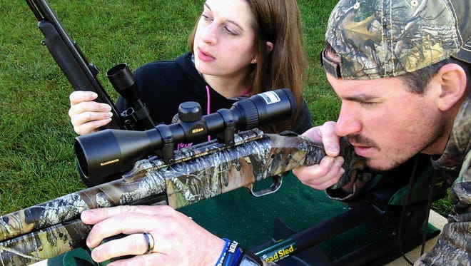 Hunting deer has been a bond for Tristan and Ryan Ellis of North Liberty for most of their ten-year marriage.  She holds her Thompson muzzle loader while he displays his Mossberg shotgun in a lead sled used for sighting-in the guns.