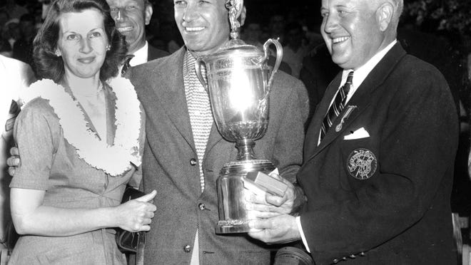In this June 11, 1950, file photo, Ben Hogan, center, smiles over a crowd and poses with his wife, Valerie, left, as he receives the U.S. Open Golf Championship trophy from James D. Standish, Jr., Detroit president of the United States Golf Association, in Ardmore, Pa.