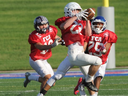 The Red team's Patrick Nash of Brownwood picks off Quay Stokes' pass in the first quarter as K.J. Kelley (25) of Cooper and Bode McMillan (12) Irion County look on. The Red team beat the Blue 21-7 in the annual FCA Myrle Greathouse All-Star Classic on Saturday, June 9, 2018 at Shotwell Stadium.