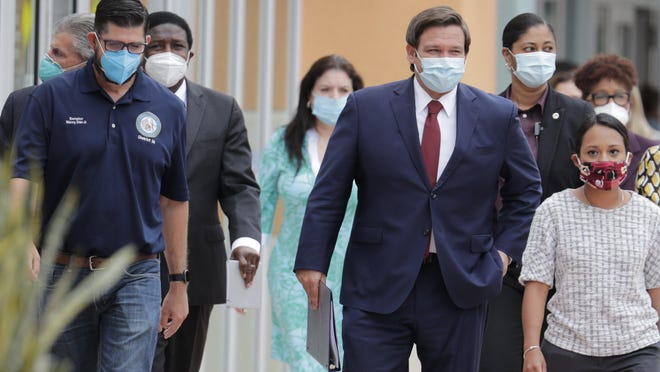 Gov. Ron DeSantis, center, arrives for a news conference Thursday in Doral, where he hinted he would roll back restrictions on businesses throughout Florida.