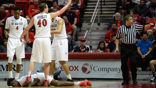 San Diego State forward Dwayne Polee II (5) lays on the court as forward Matt Shrigley (40) motions for helps as guard Dakarai Allen (4) and forward J.J. O'Brien (20) look on during the first half against the UC Riverside on Dec. 22. Polee II is traveling with SDSU again, but not playing.