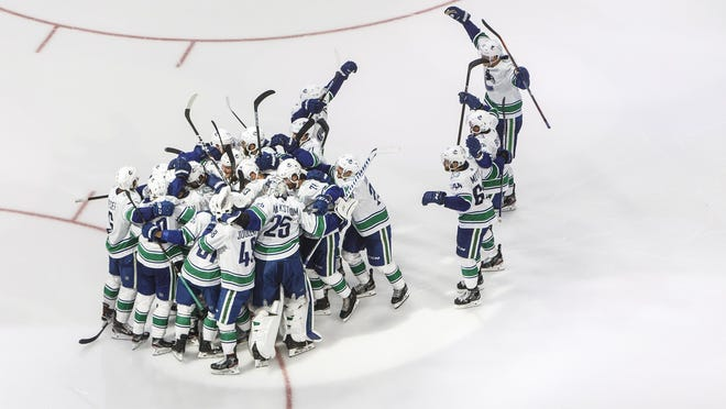 Vancouver Canucks players celebrate the win over the Minnesota Wild in overtime during an NHL qualifying round game Friday in Edmonton.