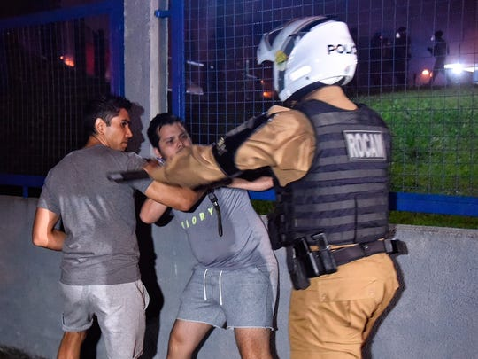 A police officer pushes supporters of Brazil's former