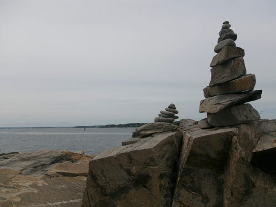Rock cairns stand on the shore of the coast of Maine