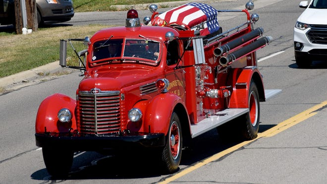 An American flag is draped over the casket of Monroe Township Fire Department Capt. Joseph Liedel on the back of an antique fire truck.