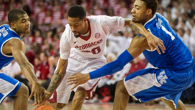 Kentucky guards James Young and Aaron Harrison attempt to steal the ball from Arkansas guard Rashad Madden during the first half at Bud Walton Arena.