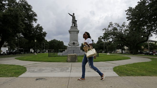 In this Sept. 2, 2015, file photo, a woman walks past a monument of Jefferson Davis on Jefferson Davis Parkway at Canal Street in New Orleans. The statue of Davis was removed by the city in May 2017. A spokesman for the city told the AP on May 19, 2017, that a story circulating online that the statue would be replaced with one of former President Barack Obama is false.