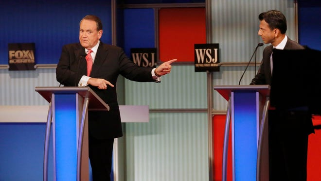 Mike Huckabee, left, makes a point as Bobby Jindal listens during Republican presidential debate at Milwaukee Theatre, Tuesday, Nov. 10, 2015, in Milwaukee.