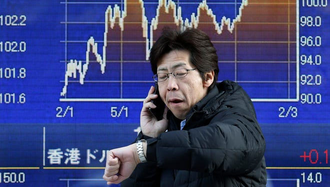 A man talks on the mobile phone in front of an electronic stock board of a securities firm in Tokyo on Feb. 18.