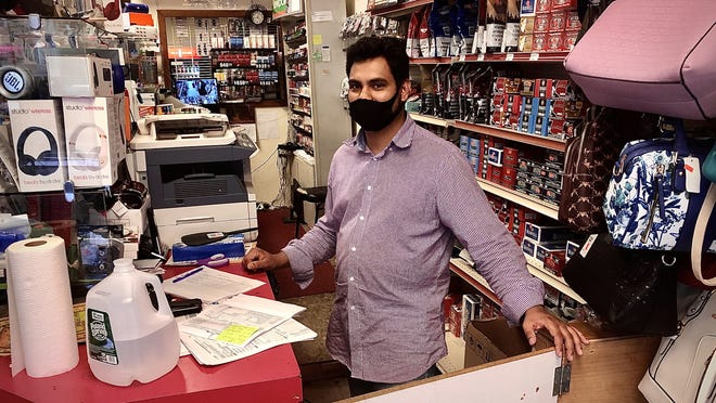 Abdul Shopan, owner of Neighborhood Variety on North Main Street in Fall River, says that he's not always able to get coins from his local bank.  Herald News photo by Charles Winokoor