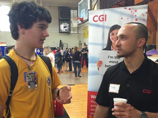 Andrew Abshire, a student at Paul Breaux Middle, meets with a representative from CGI at the school's college and career day Thursday.