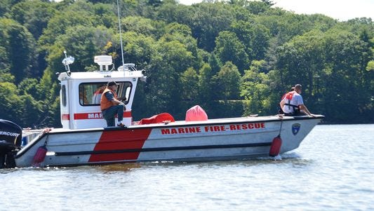 Searchers aboard a rescue boat look near Norrie Point in Staatsburg Saturday for missing kayaker Ian Jones.