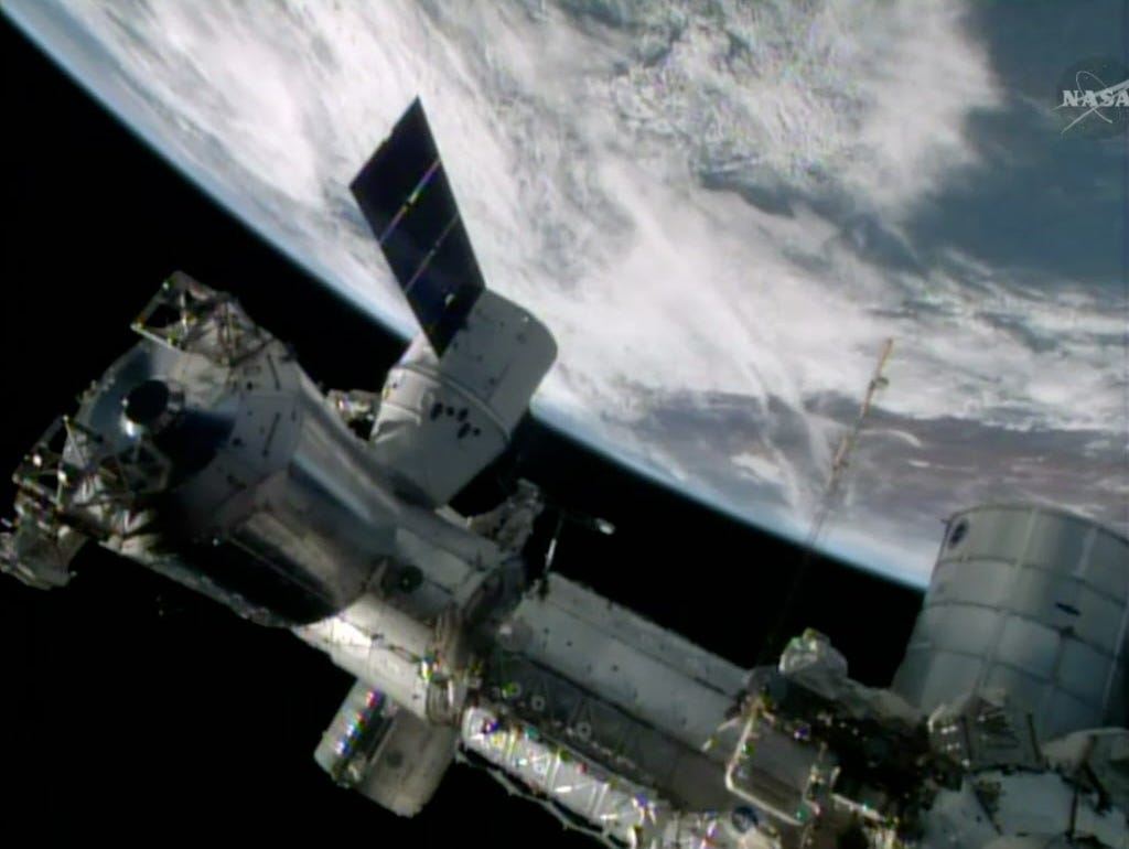 FILE- In this April 20, 2014, image made from a frame grabbed from NASA-TV, the SpaceX Dragon resupply capsule begins the process of being berthed on to the International Space Station. Astronauts hurriedly evacuated the U.S. section of the Internati
