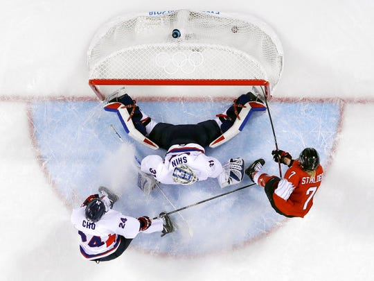 Lara Stalder, of Switzerland, scores a goal against South Korea's goalie Shin So-jung and Cho Mihwan, of the combined Koreas team, during the third period of the preliminary round of the women's hockey game at the 2018 Winter Olympics in Gangneung, South Korea.