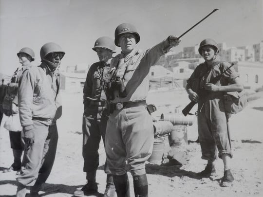 Gen. George S. Patton points his riding crop during