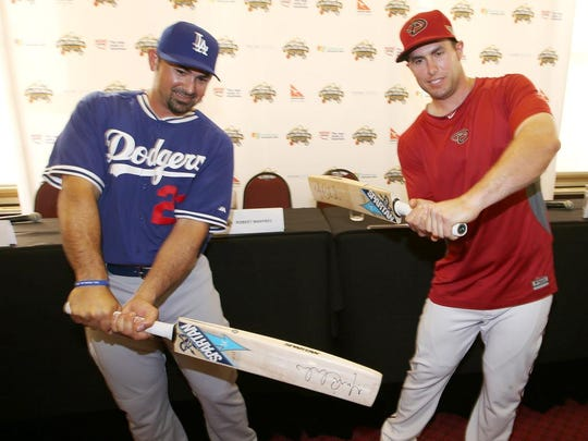 The Dodgers' Adrian Gonzalez (left) and the Diamondbacks' Paul Goldschmidt try swinging cricket bats while in Australia.