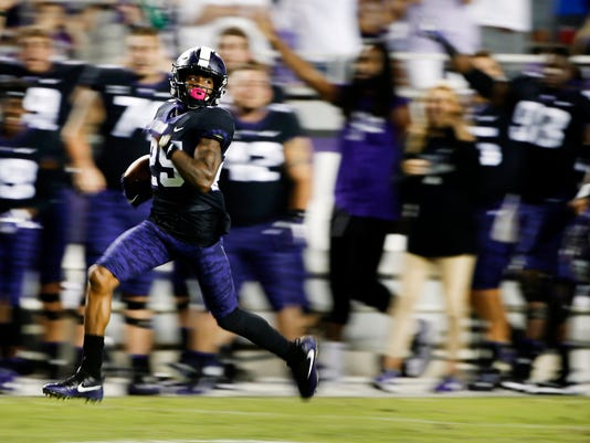 FILE - In this Saturday, Oct. 21, 2017, file photo, TCU's KaVontae Turpin returns a punt 90 yards for a touchdown as Kansas' Chase Harrell (3) during the second half of an NCAA college football game in Fort Worth, Texas. Turpin has returned kicks for touchdowns in each of the last two games for TCU. (AP Photo/Ron Jenkins, File)