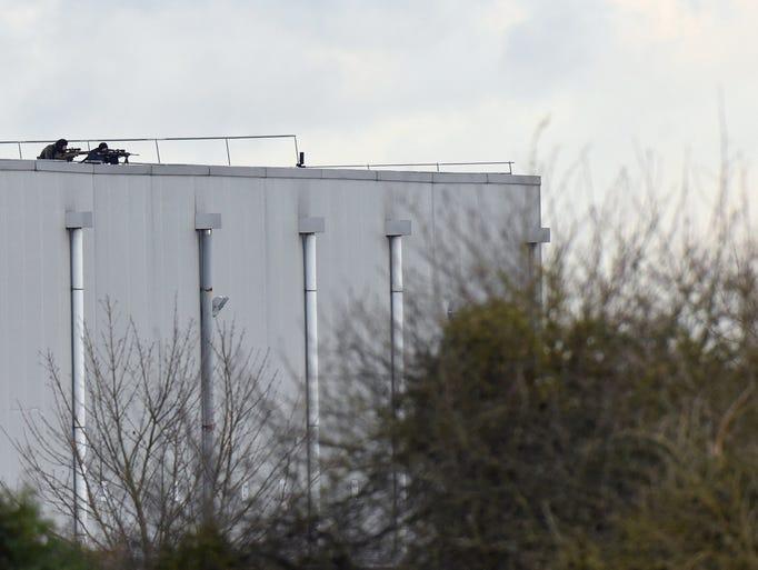 Police marksmen take up a position on a roof in Dammartin-en-Goele,