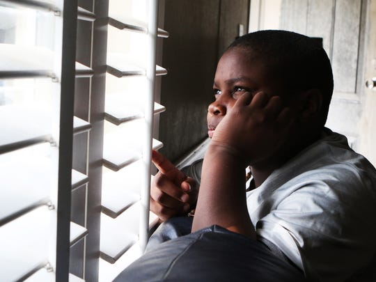 Deangelo Brown Jr., 11, watches the neighbors out the window of his grandmother's home in Ruston on Friday, November 4, 2016.