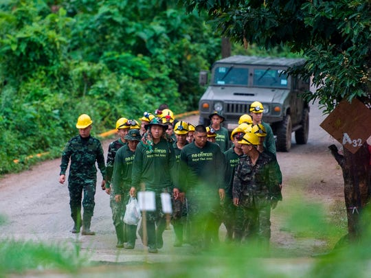Thai soldiers walk out from the Tham Luang cave area