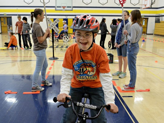 J.J. Back rides a glider bike through an obstacle course