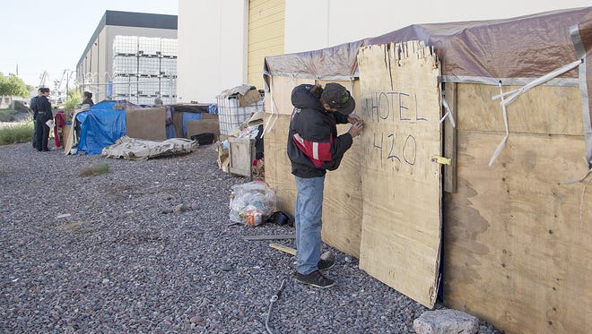 Troy Nicholson, a homeless man, made a wooden shelter for his family near the bridge in downtown Phoenix.
